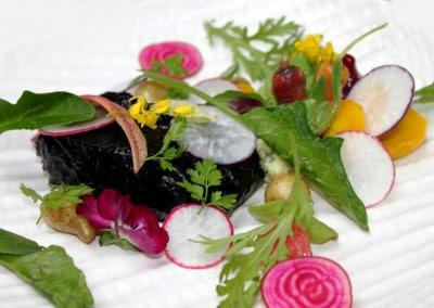 Chef Nic Poelaert's Bass Cooked in Squid with Vegetables, a Burnt Carrot Puree & Citrus